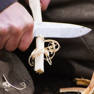 Survivalist making feather sticks from a piece of pinewood with a bushcraft knife