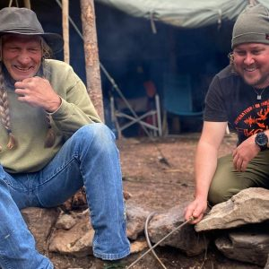 Two survivalists laugh around a cooking fire at survival class